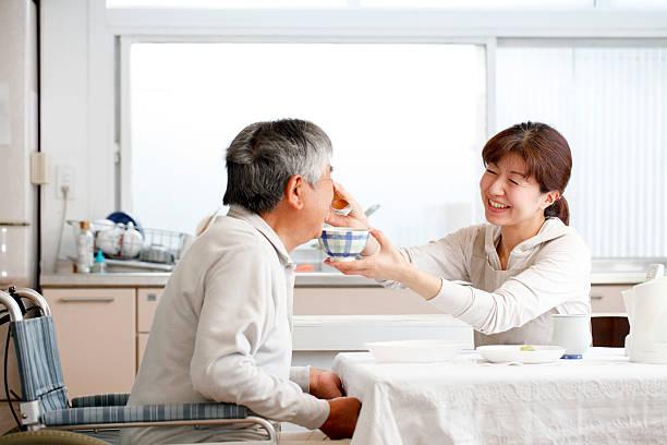 ヘルプに食事 - 高齢者介護 ストックフォトと画像