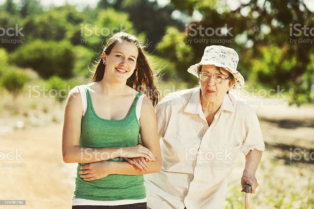 Helped by young companion, old woman walks through forest stock photo