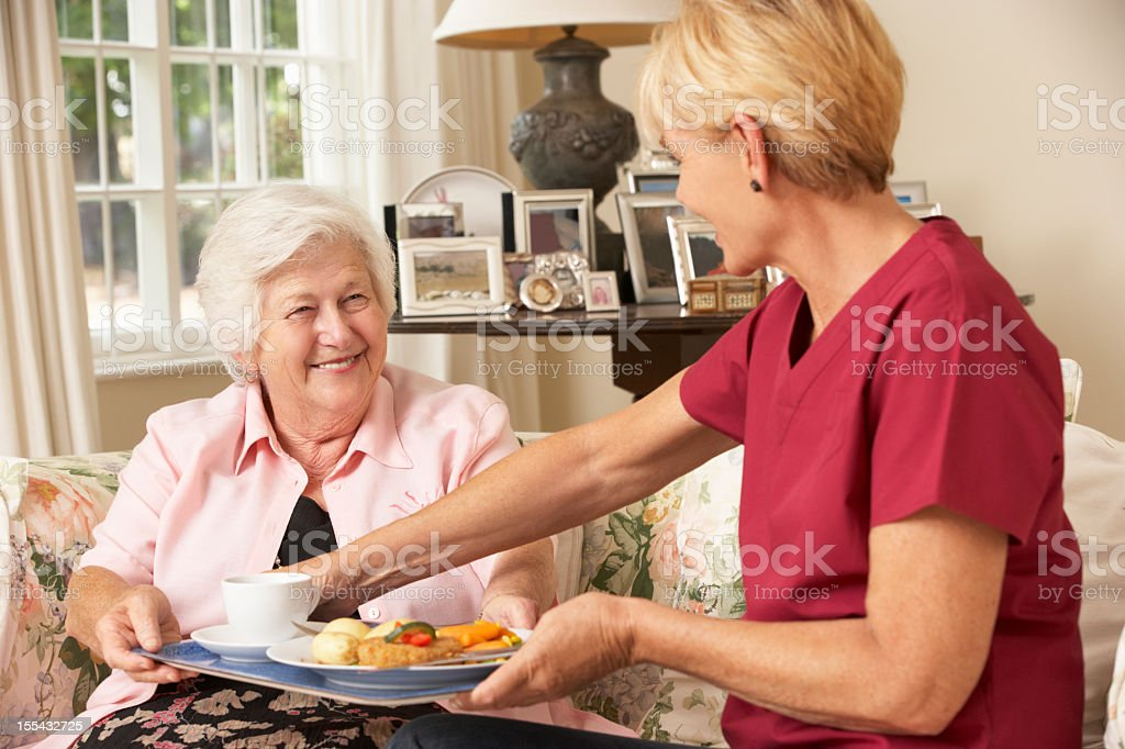 Helper Serving Senior Woman With Meal In Care Home stock photo