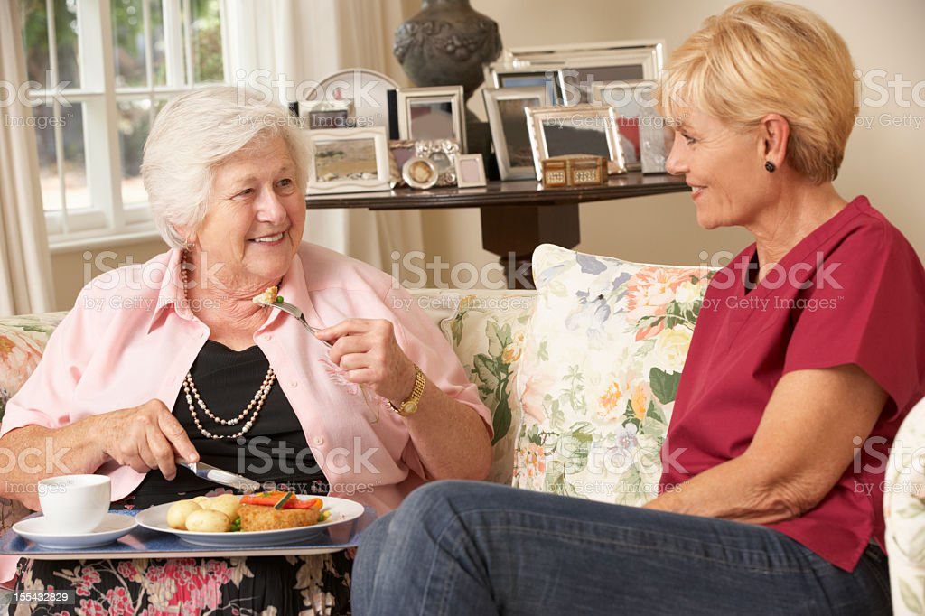 Helper Serving Senior Woman With Meal In Care Home royalty-free stock photo