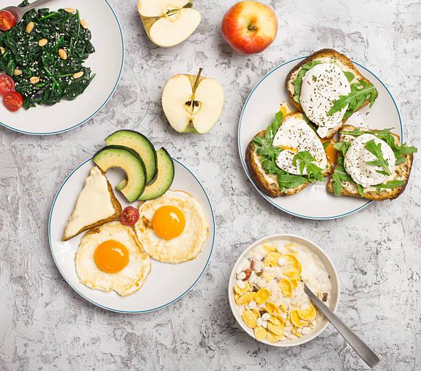 helpful breakfast from different of dishes on light surface - gefüllte eier stock-fotos und bilder