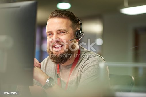 a call centre phone operative in his mid 30s chats on the phone at his desk . He is explaining something to the person on the phone in a friendly manner . behind him a defocussed office interior can be seen . This could be a call centre or an office worker chatting to a customer .