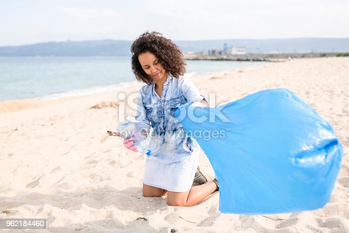 962184460 istock photo Helpful lady during local clean up at the beach 962184460