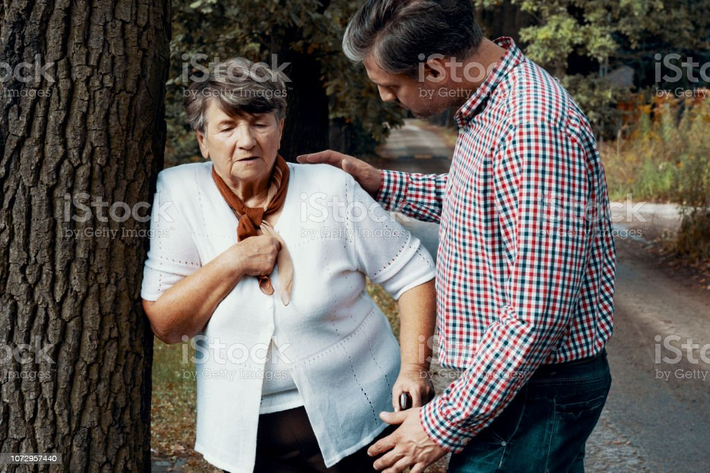 Helpful pedestrian taking care of senior woman having heart attack on the street stock photo