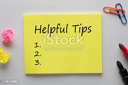 Helpful Tips text on note with marker pen and various stationery. Business concept