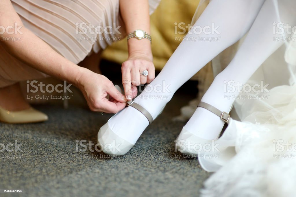 Helping a bride to put her wedding shoes on stock photo