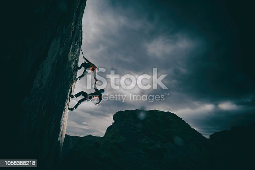 Two climbers on a cliff. Friend catches partner as he falls off the mountain. Helping each other.
