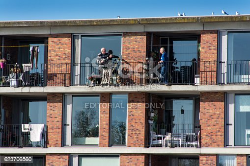 Utrecht, The Netherlands - Octoberber 31, 2016: Two elderly people are talking to each other at the neigbouring balconies of their appartment building in the new suburb Leidsche Rijn.