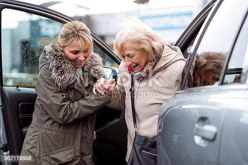 A mature woman helps a senior woman out of a car as she takes her to the shops