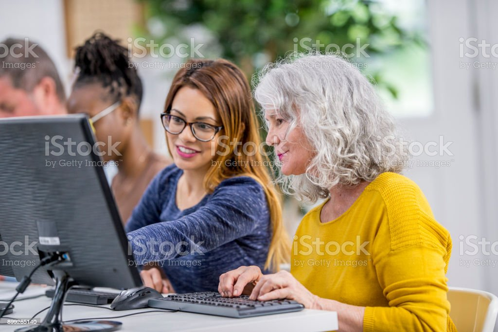 Helping A Woman Using A Computer stock photo