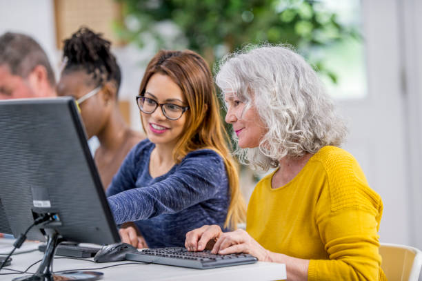 helping a woman using a computer - adult education stock pictures, royalty-free photos & images