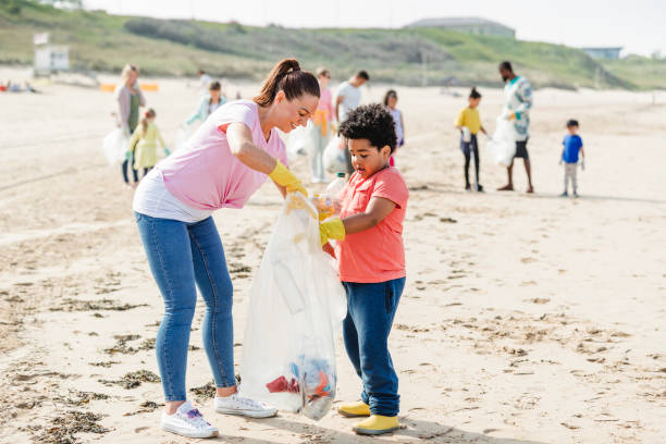 Helping Children Clean Up Their Beach Collecting rubbish off a beach. Plastic containers, bottles in their bag. They are using a mechanical grabber. Mother and daughter working together environmental cleanup stock pictures, royalty-free photos & images