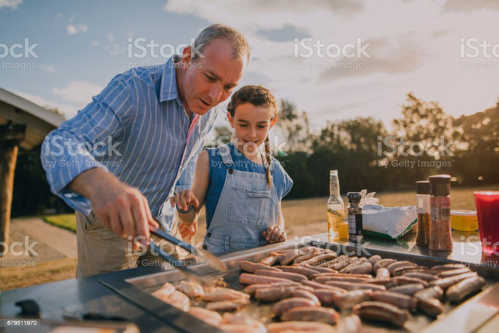 Helping Dad Cook Sausages on the BBQ stock photo