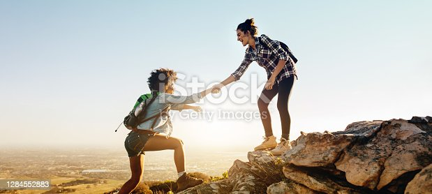 istock Helping each other to the top of mountain 1284552883