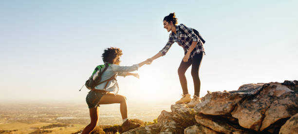 Helping each other to the top of mountain stock photo