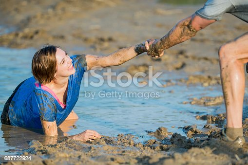 687723318istockphoto Helping Hand in a Mud Run 687722924