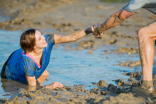 687723318 istock photo Helping Hand in a Mud Run 687722924