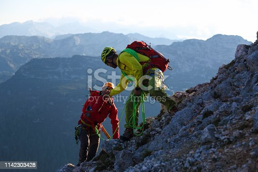 Male mountain climber is helping his friend to the top.