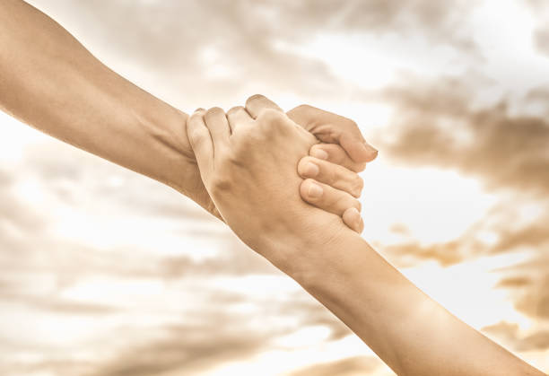 Helping hand on sunset background, stock photo