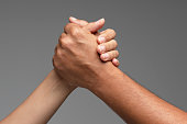 Two unrecognizable caucasian peoples hands are holding each other in front of gray background.
