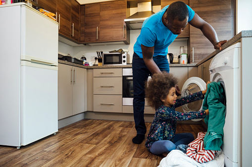 Wide shot of a mixed race girl sitting on the floor in the kitchen and helping her father put the washing into the washing machine.