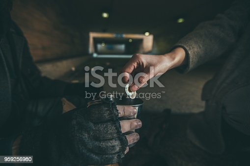One man, young homeless on the street begging, woman handing him some money, part of