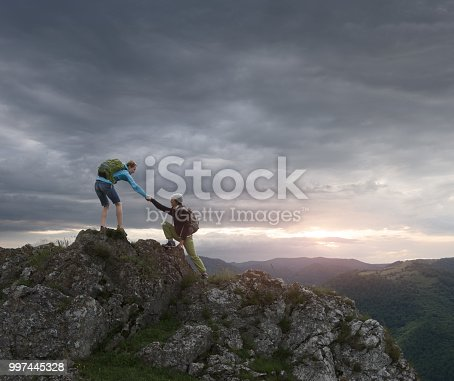 Hiker Woman helping her friend reach the top of the mountain