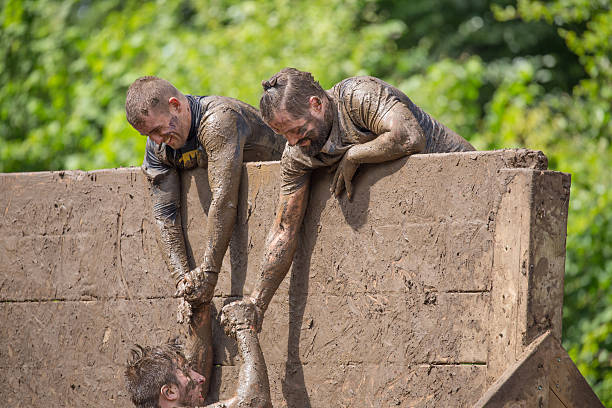Helping hand to climb a slippery wall Сirencester, England - August 21, 2016: Helping hand for a man as he attempts to climb a slippery wall during his gruelling 12 mile assault course of the 'Tough Mudder' challenge in Cirencester park, Gloucestershire. This annual event is a team-based 10-12 mile obstacle course designed to test physical strength endurance and teamwork.  mud run stock pictures, royalty-free photos & images
