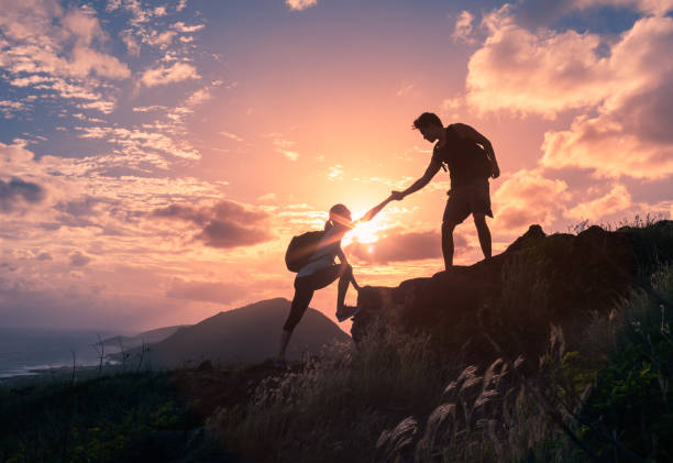 Helping hikers Male and female hikers climbing up mountain cliff and one of them giving helping hand. passion stock pictures, royalty-free photos & images