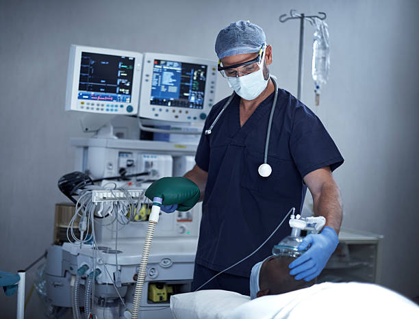 Helping him to breathe Shot of a surgeon using an oxygen mask on a patient during surgery anesthetize stock pictures, royalty-free photos & images