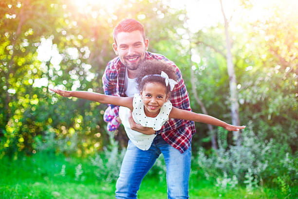 helping his daughter fly! - african youth jumping for joy stock photos and pictures