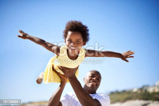 A father lifting his adorable daughter into the air while enjoying a day at the beach