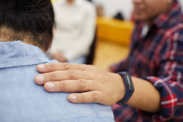 Helping in Support Group Closeup of young man crying in support group with psychologist comforting him, copy space drug rehab stock pictures, royalty-free photos & images