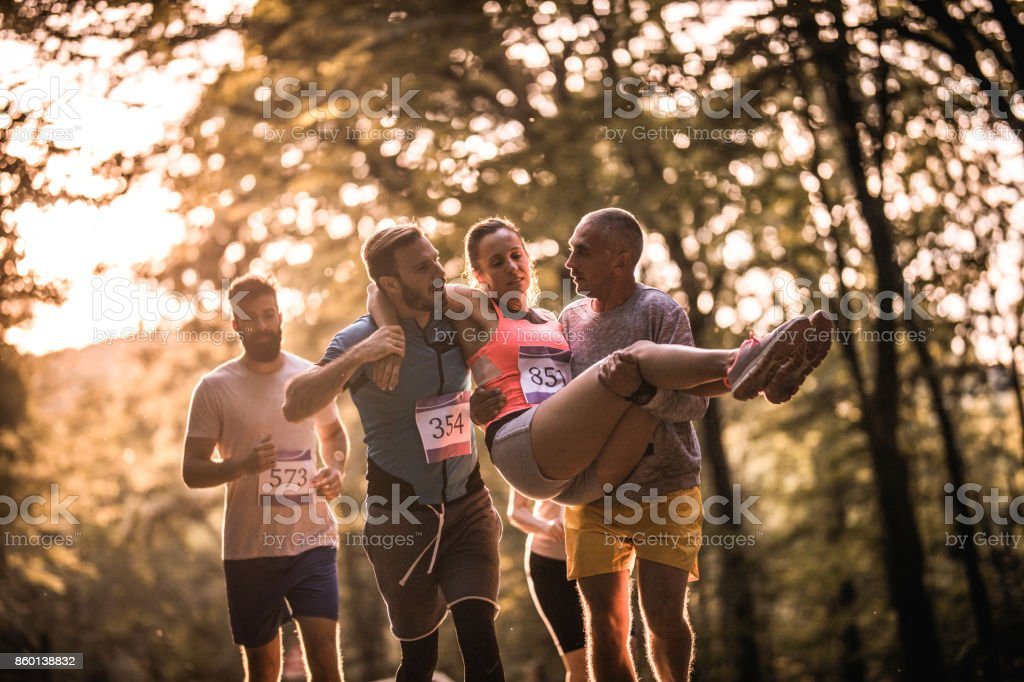 Helping injured marathon runner! stock photo