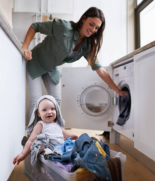 helping mommy with her chores - laundry laundry room stock photos and pictures
