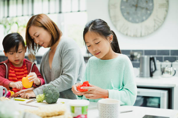 helping mum to prepare the dinner - east asian ethnicity stock photos and pictures