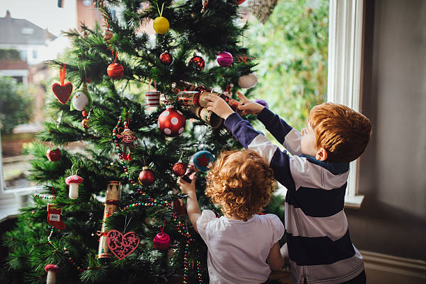 helping mum with the tree - ornamentik stock-fotos und bilder