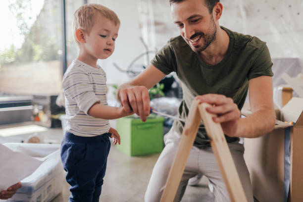 Helping my dad Photo of a young father with his little boy, assembling furniture together after moving into their new home diy stock pictures, royalty-free photos & images