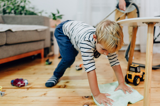 Photo of a little boy and his mother, deep cleaning their home due to coronavirus pandemic
