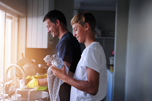 Helping out with household chores Cropped shot of a father and son cleaning dishes together at home chores stock pictures, royalty-free photos & images