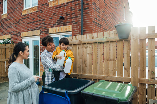 Three generation family of a father daughter and grandson standing outside disposing of household recycling into an outdoor bin. The young boy is helping while learning about recycling.