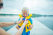 A mother is helping her son put on a life jacket. He is about to go swimming.