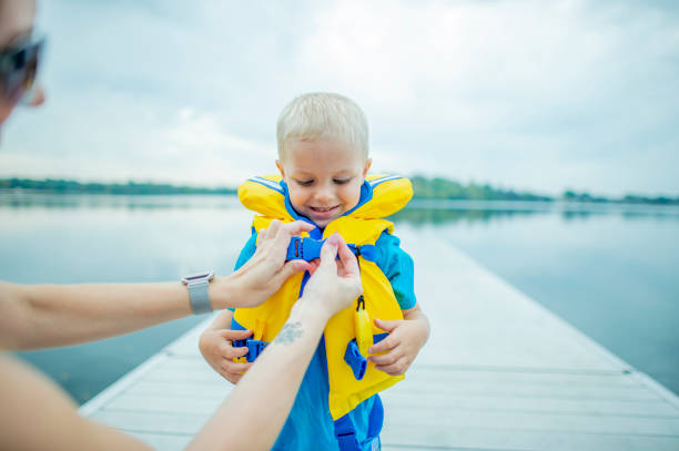 Helping Son With Life Jacket stock photo