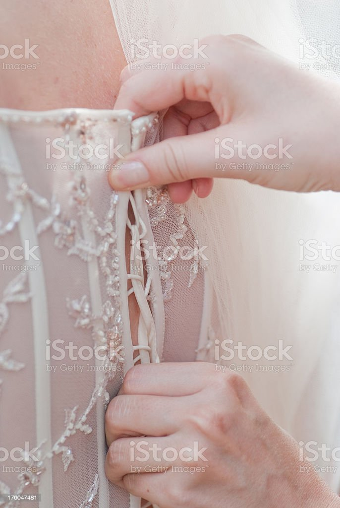 helping the bride with wedding dress royalty-free stock photo