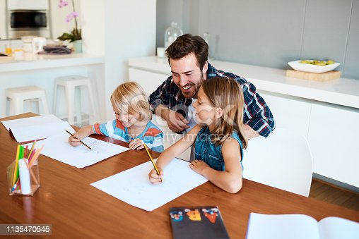Shot of a young father helping his two small children with their homework at home