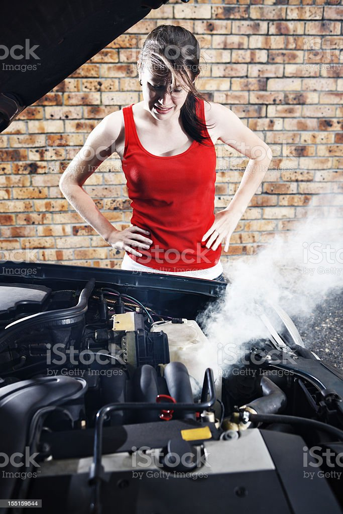 Helpless and hopeless: stranded brunette with broken down auto royalty-free stock photo
