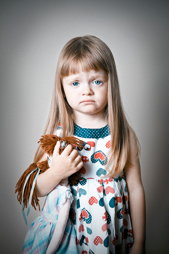 The cutest yet saddest little girl holding her favorite doll, looking at the camera. Grain (background) and vignetting added for a dramatic effect.