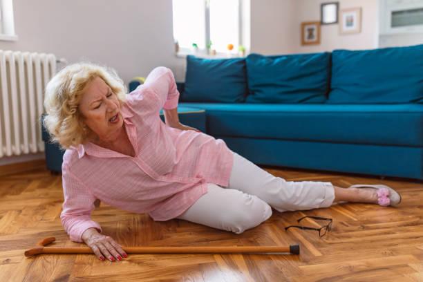 Femme retraité impuissant avec le cheveu blond se reposant sur l'étage à la maison. Les risques qui viennent avec le vieillissement. - Photo