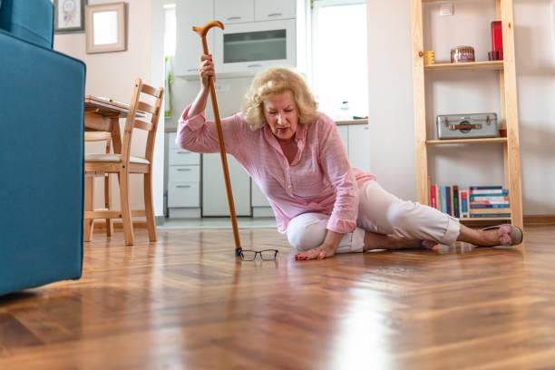 Femme retraitée impuissante avec le cheveu blond s'asseyant sur l'étage à la maison. Les risques qui viennent avec vieillir. - Photo