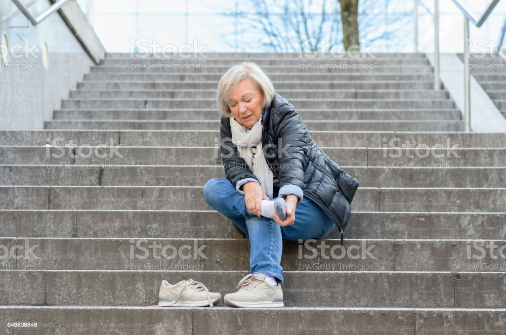 Helpless senior woman massaging her Foot stock photo